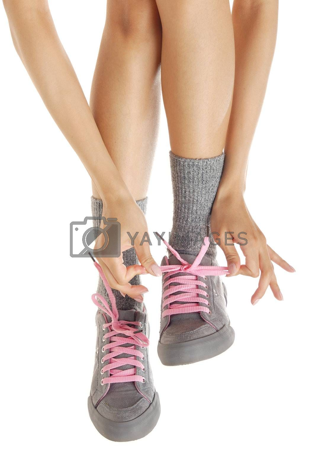 Woman legs in sport-boots and hands fastening laces