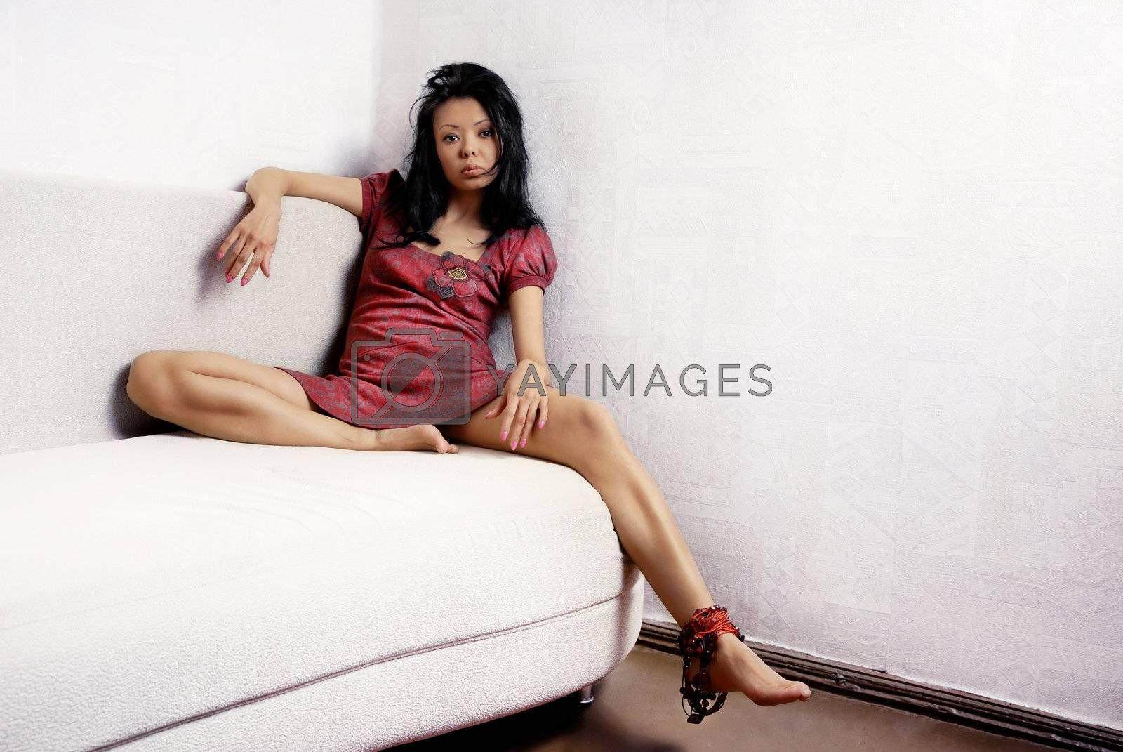 Tired woman with long legs sitting on the sofa in light room