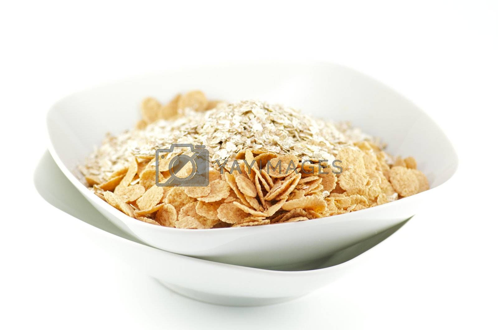 Muesli and corn flakes in white plates on white background