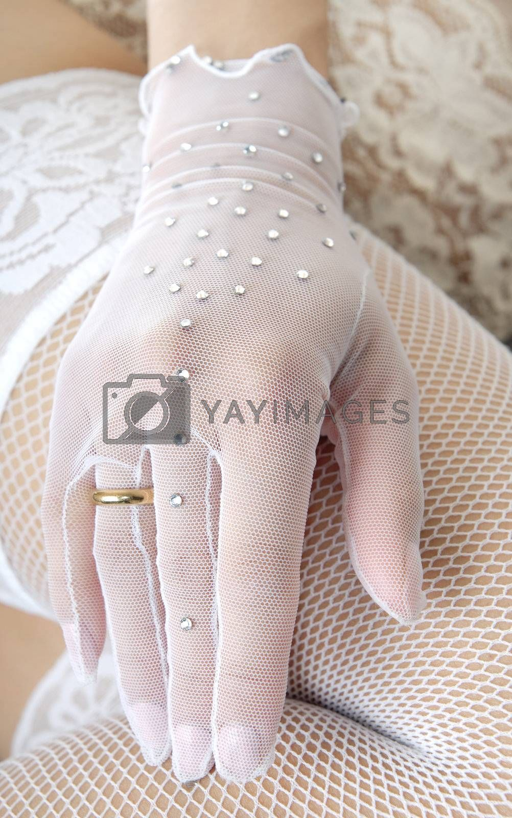 Close-up photo of the elegant hand in glove with wedding ring