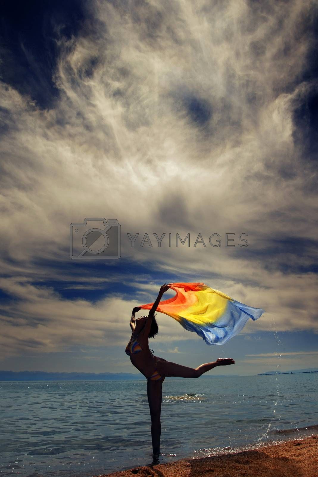 Photo of the dancing lady at the sea during vibrant sunset