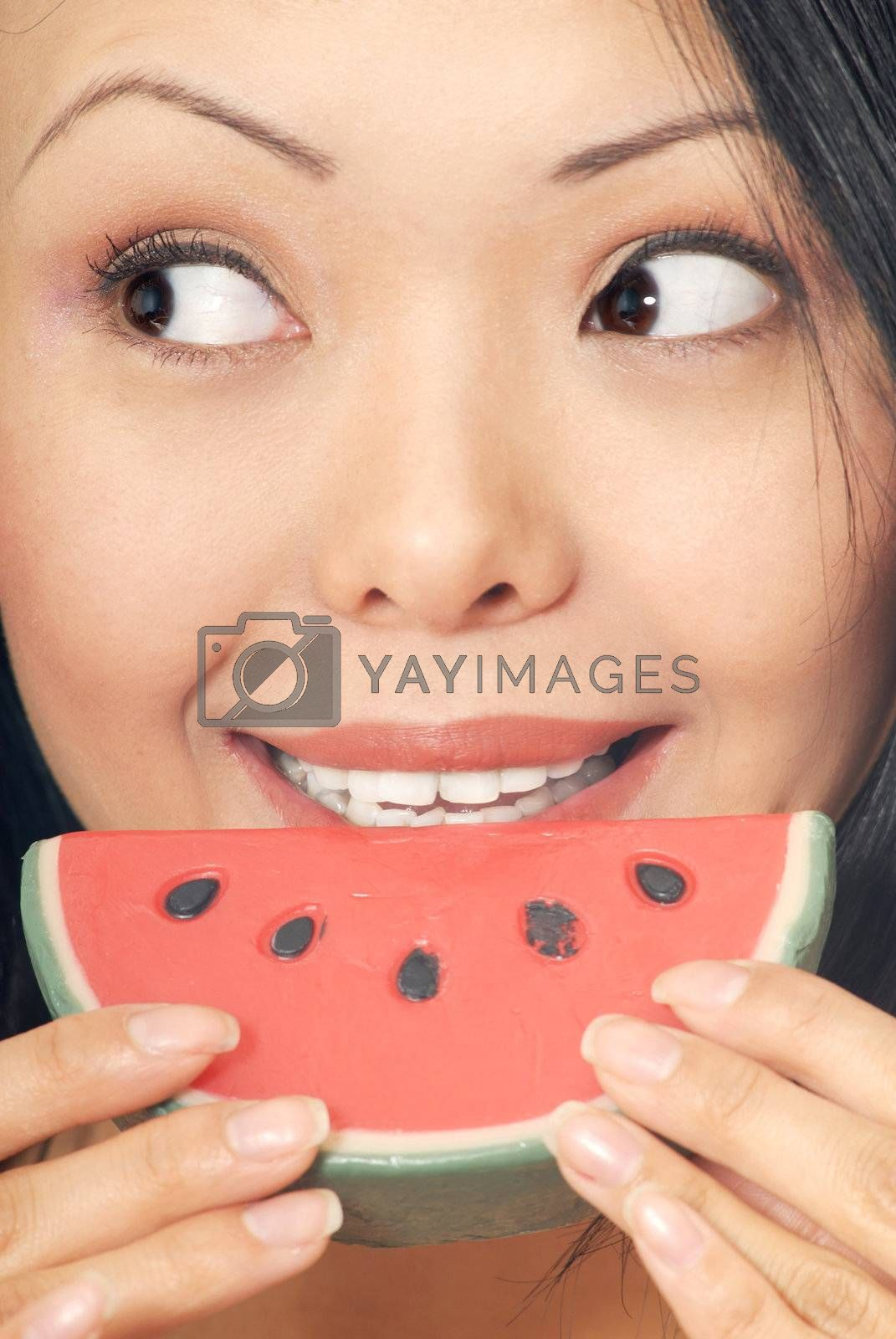 Smiling woman with melon looking to the sideward