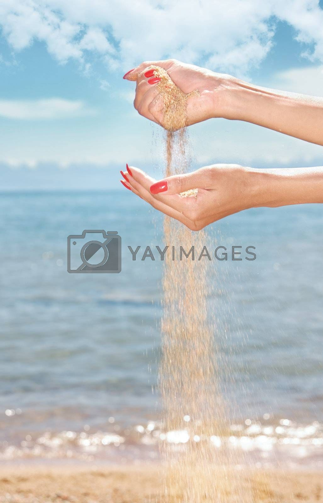 Close-up photo of the woman hands playing with sand