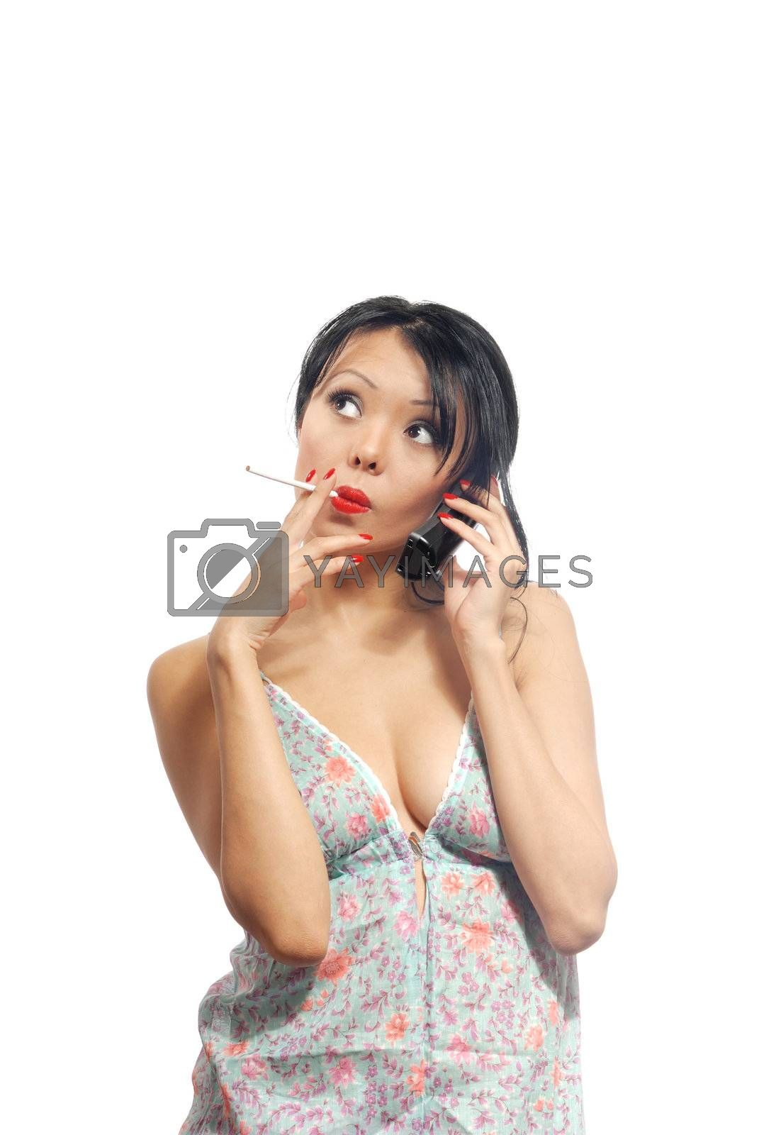 Young housewife talking via phone and smoking