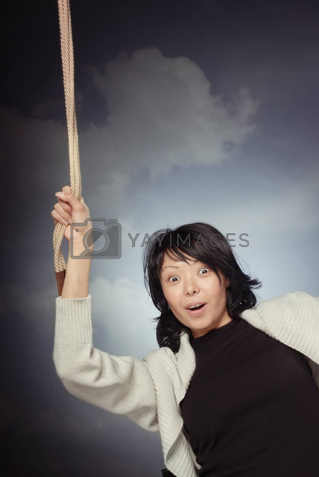Funny lady falling and holding the rope on a sky background
