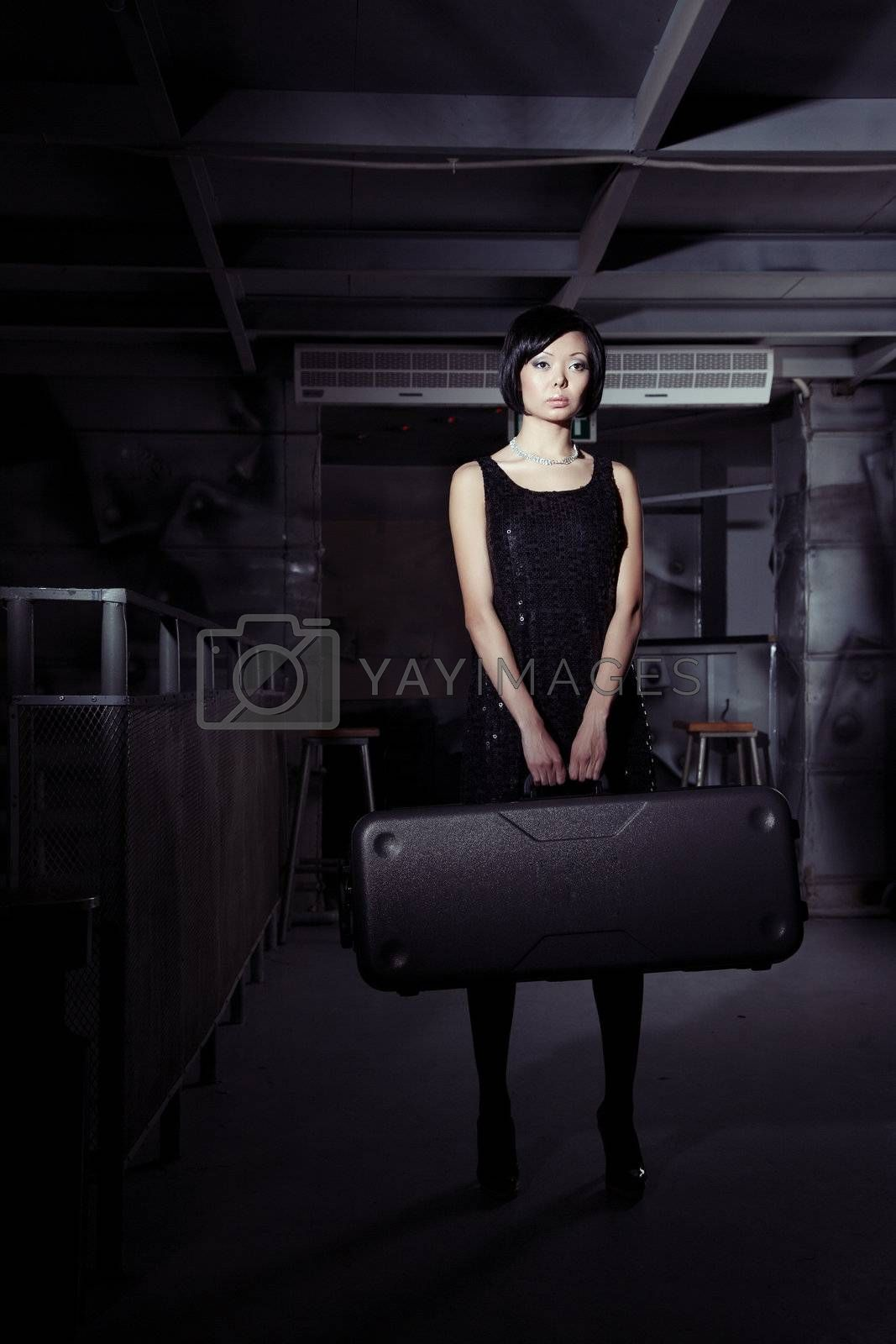 Small brunette lady holding big suitcase in the dark airport terminal