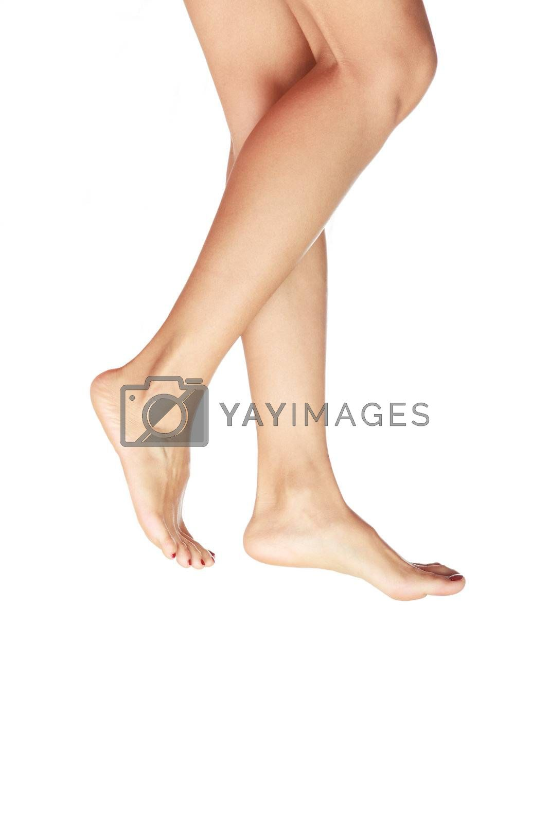 Barefoot woman legs walking on a white background