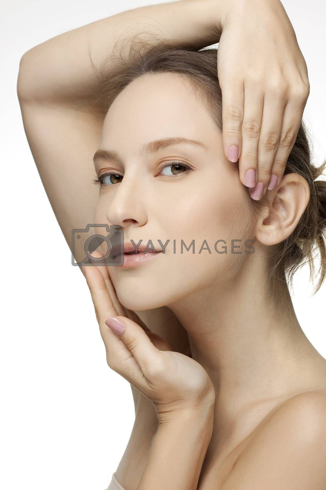 Close-up portrait of a beautiful young woman holding hands by her face