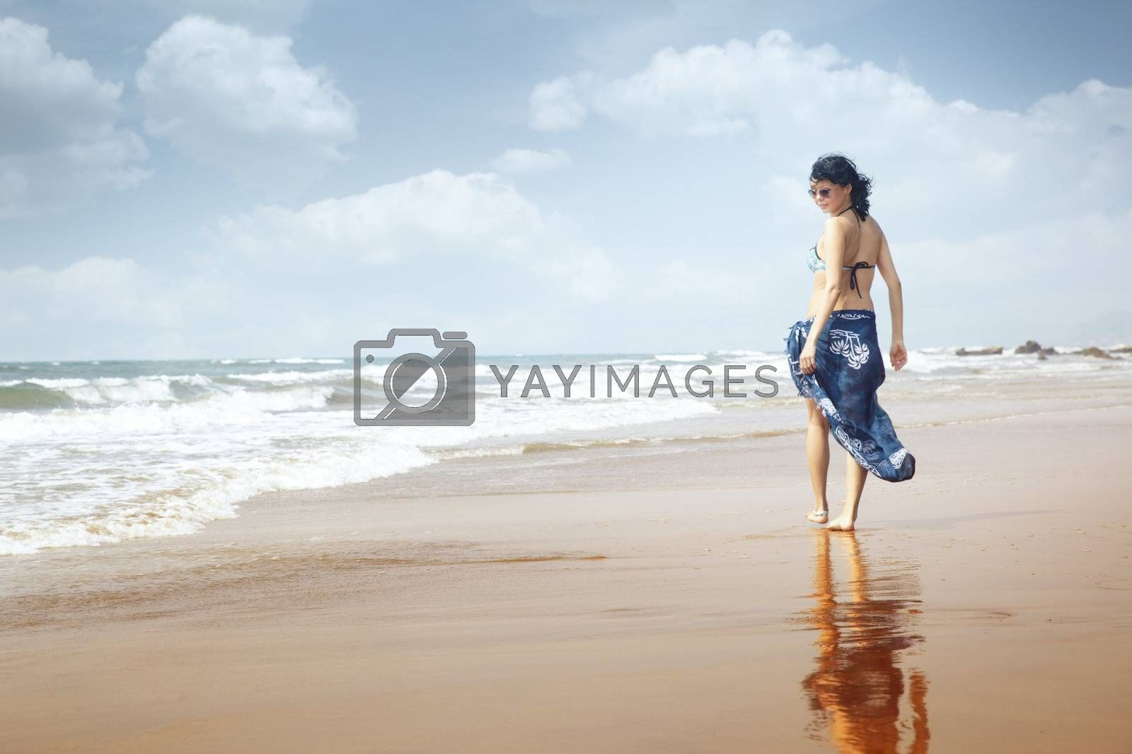 Smiling lady walking at the paradise beach. Natural light and colors