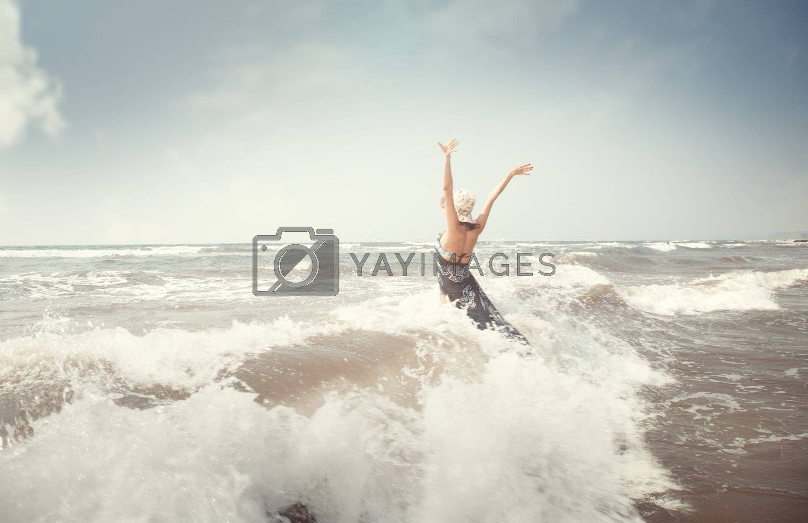 Happy brunette lady in the sea playing with waves