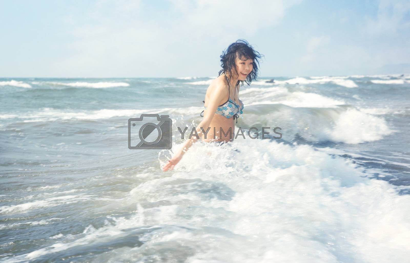 Happy brunette lady laughs and plays with water at summer beach