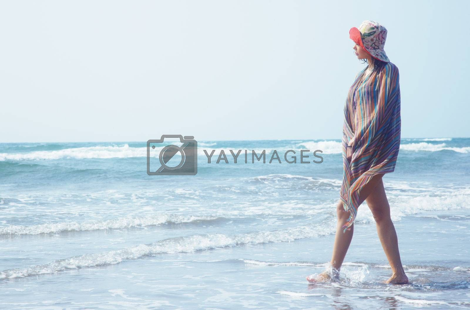 Woman with hat walking at the summer beach. Natural light and colors