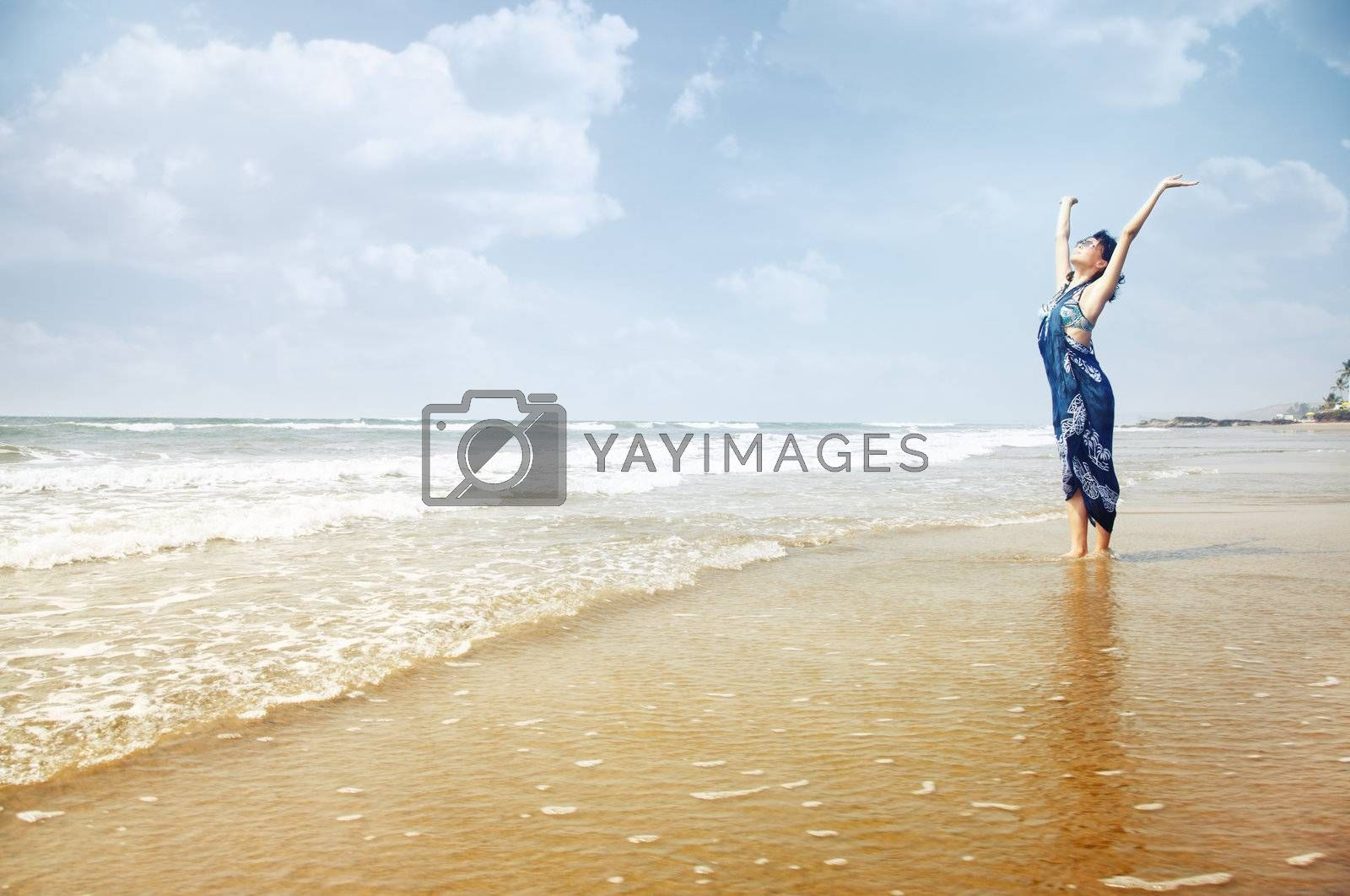 Happy lady standing in the water with hands up. Summer beach in Goa, India. Horizontal photo with vibrant colors