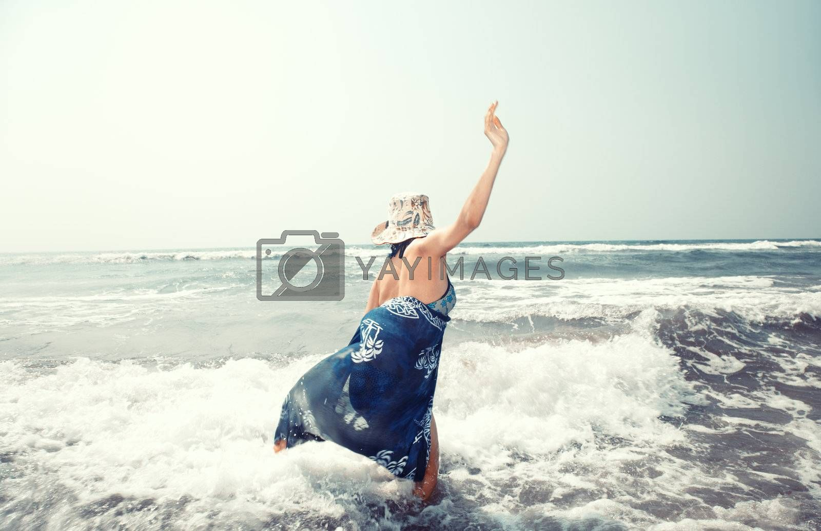 Happy lady in hat playing with waves at the sea