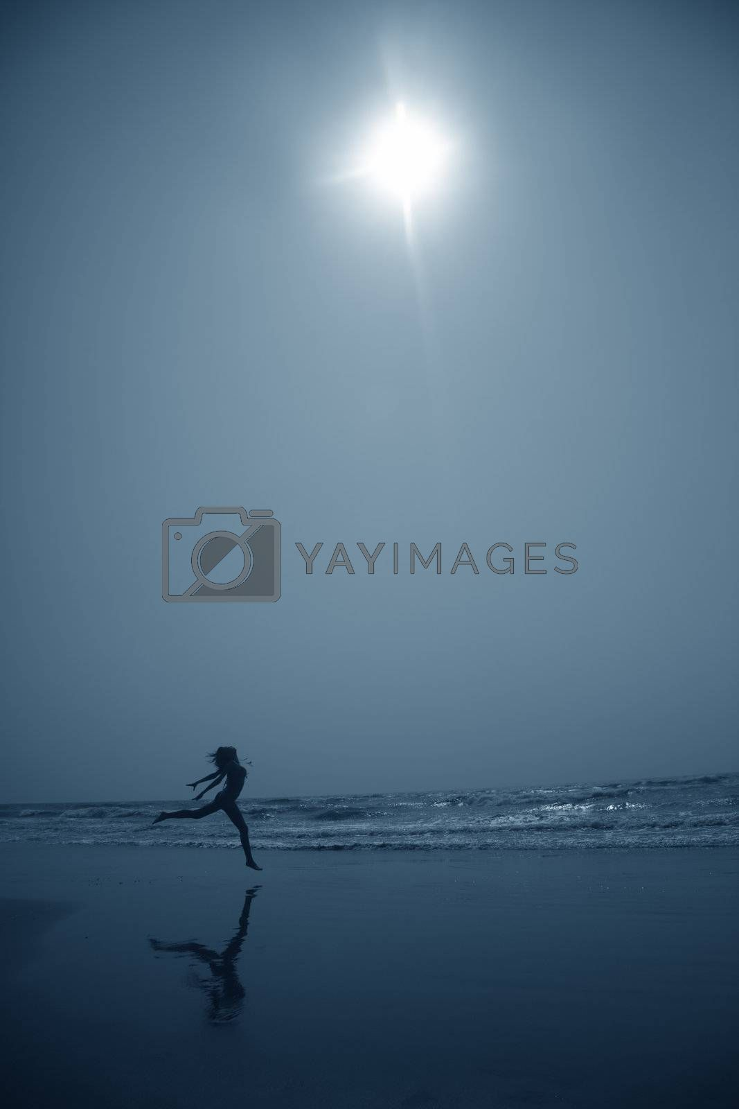 Silhouette of the lady dancing at the beach in deep dark night. Artistic blue colors toning added for coolness of the night