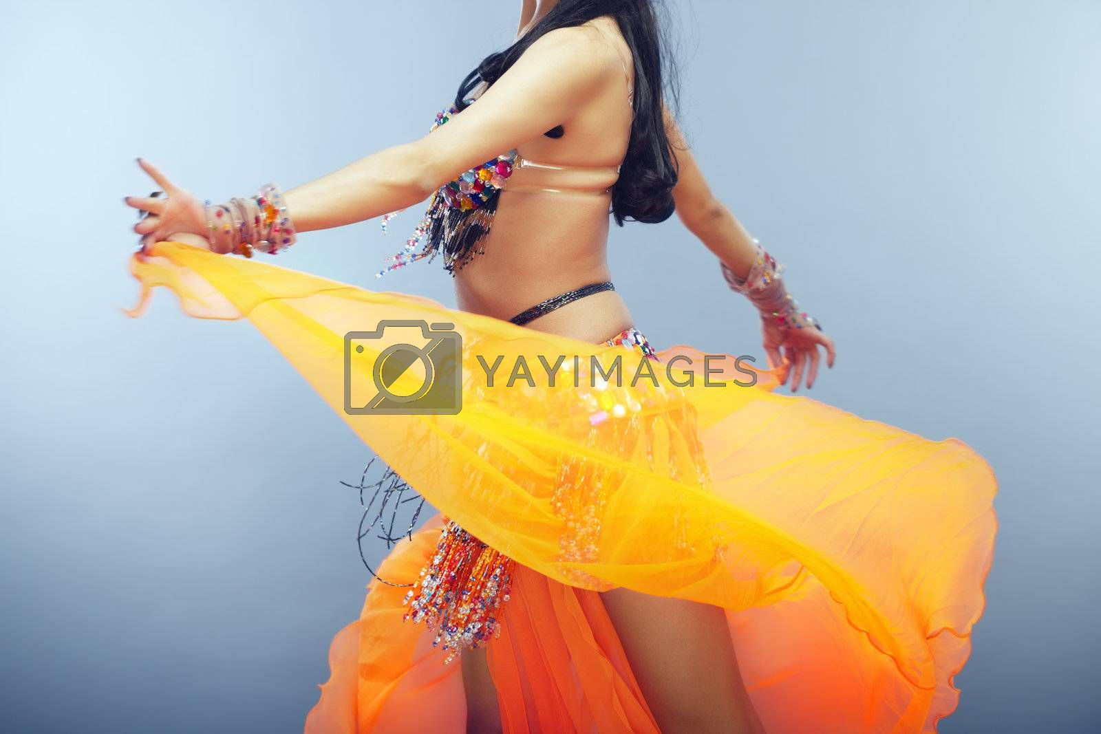 Body part of the woman dancing belly dance in traditional costume