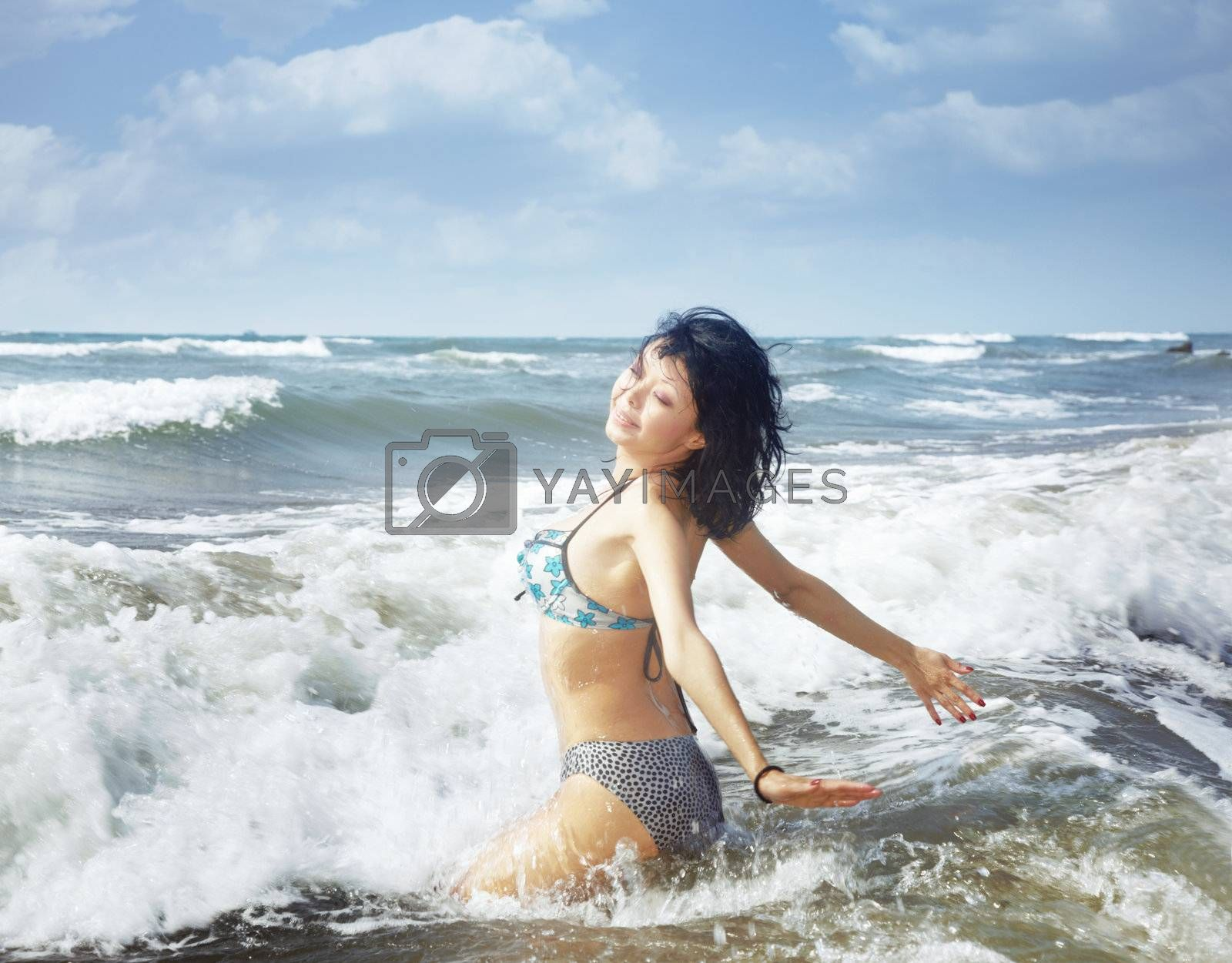 Smilig lady playing with waves at the sea resort during summer