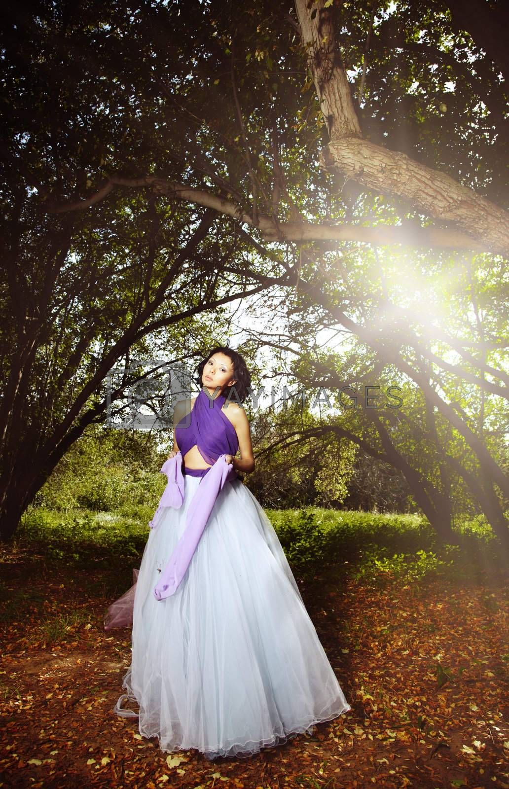 Elegant lady in the fairy autumn forest with sunlight at the background