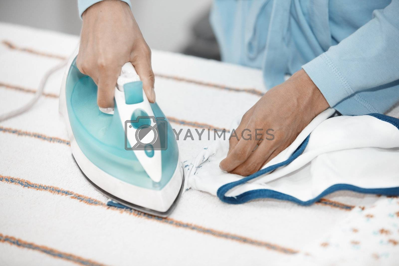 Hands of human doing housework with iron