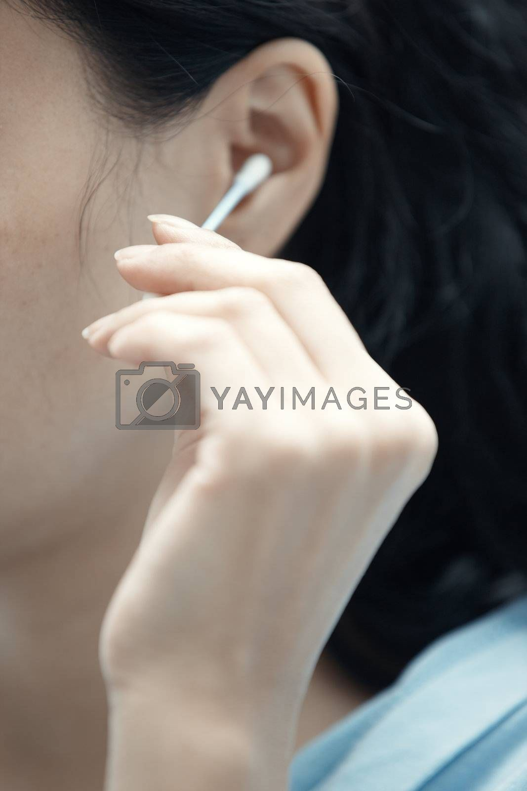 Woman holding cotton swab and cleaning ear