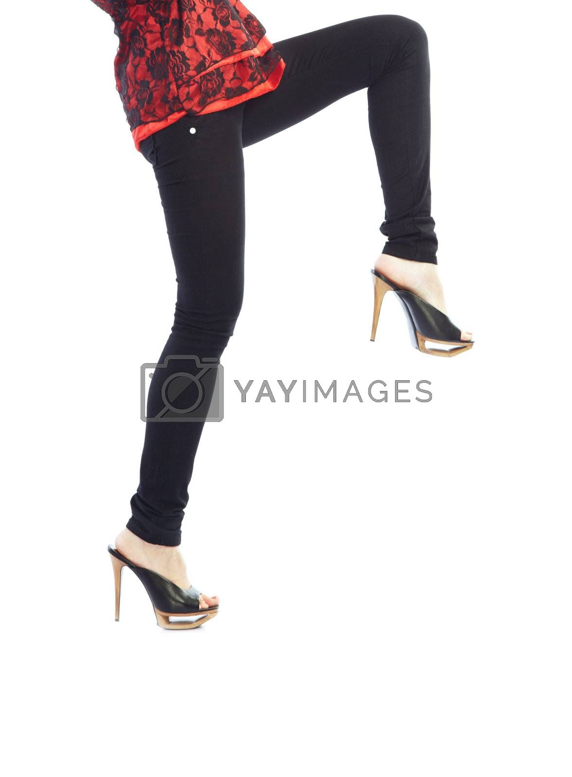 Close-up photo of woman legs in black trousers going on a white background