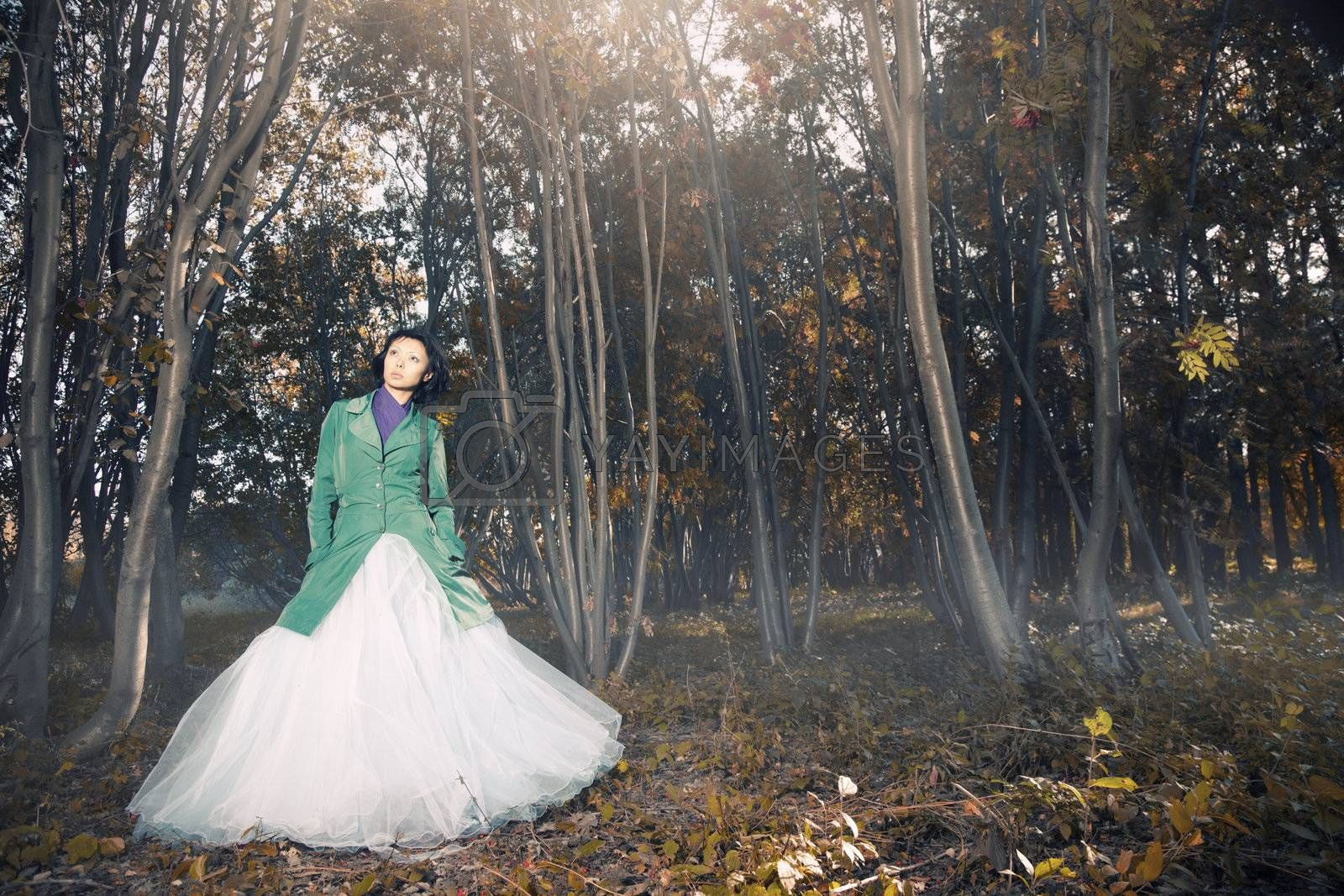 Lady in the wedding dress standing in the autumn forest with fog and red leaves