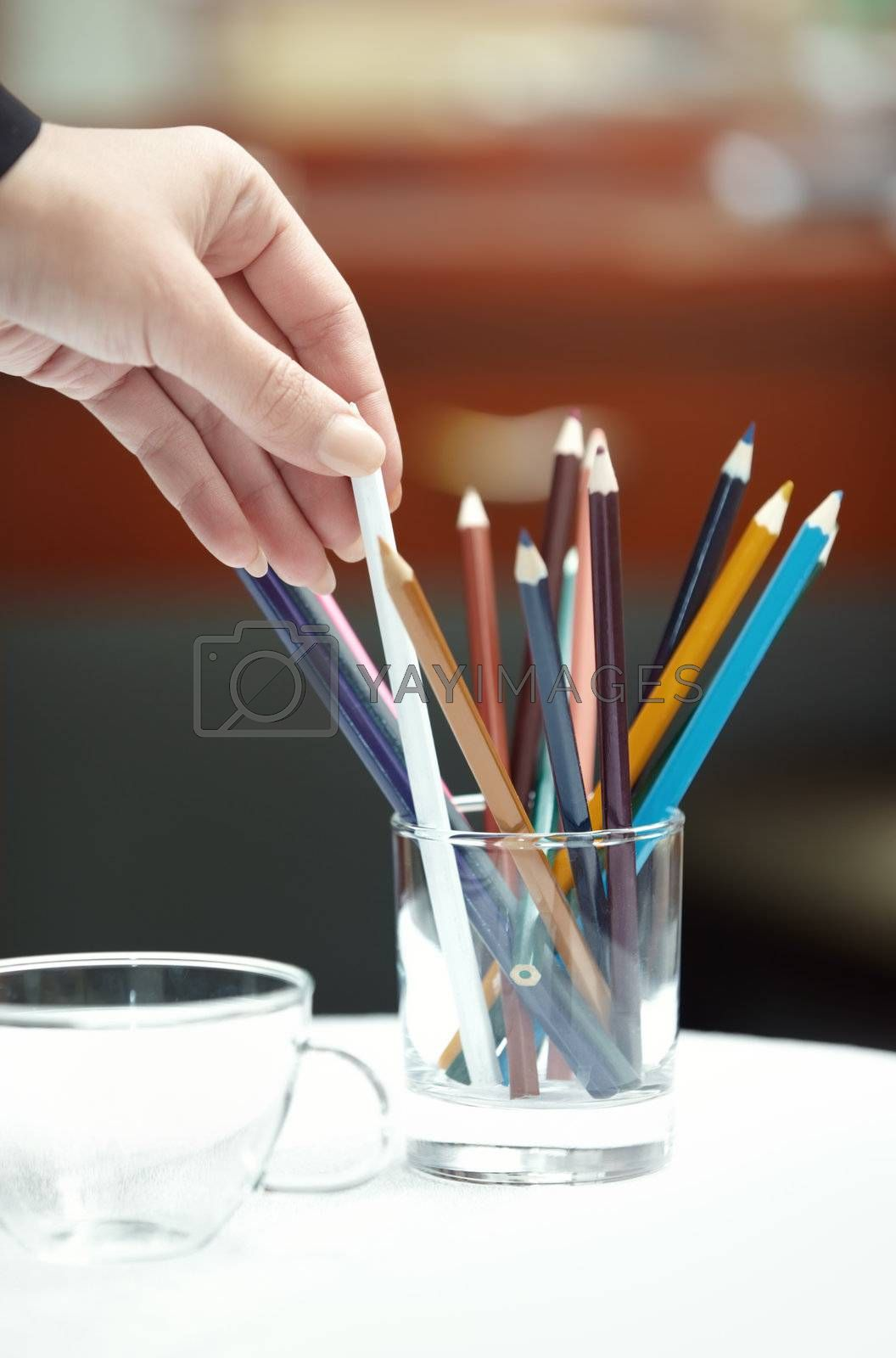 Human hand selecting colored pencil. Vertical photo