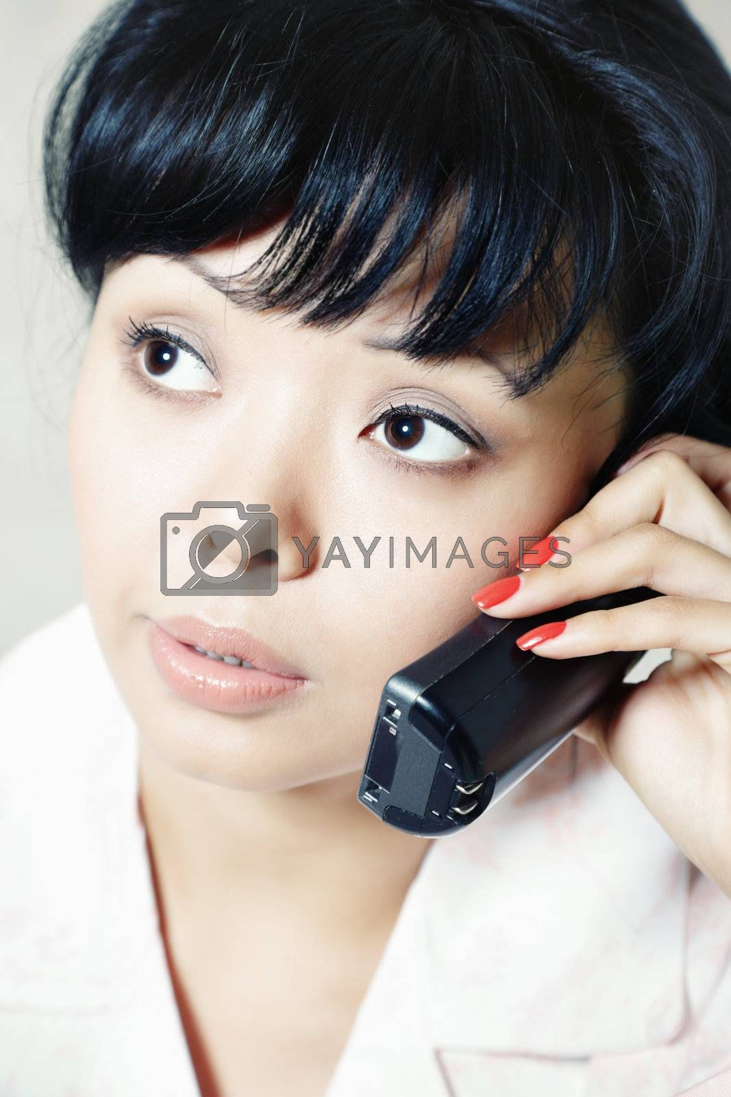 Close-up vertical portrait of the brunette indoors talking via telephone