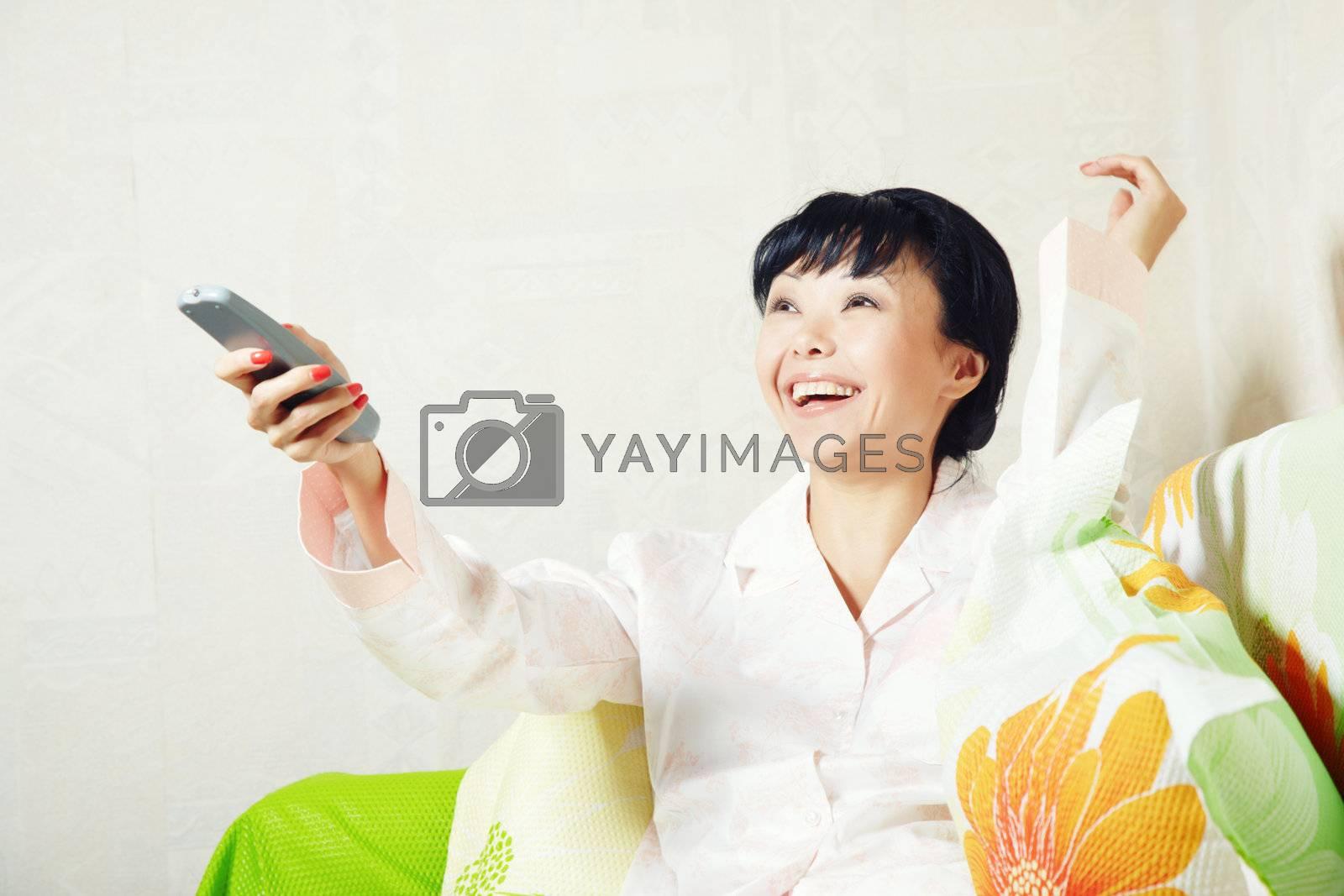 Joyful brunnete woman indoors changing TV channels