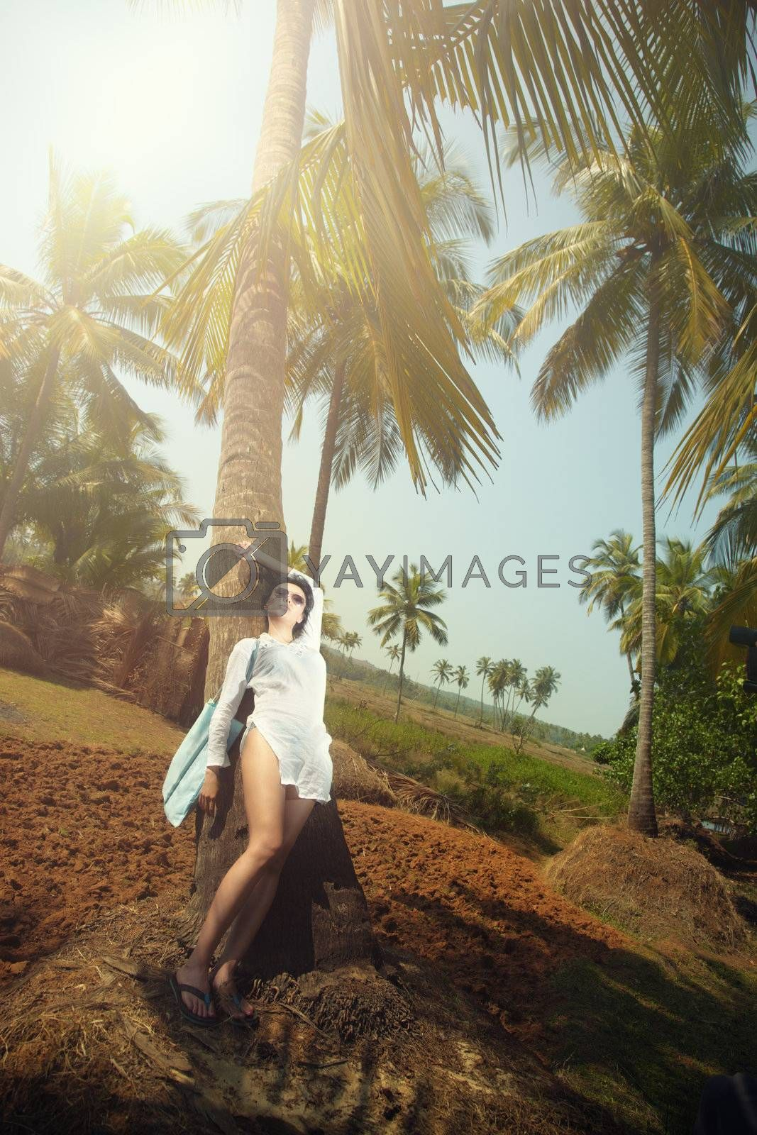 Brunette lady relaxing on a palm at exotic resort