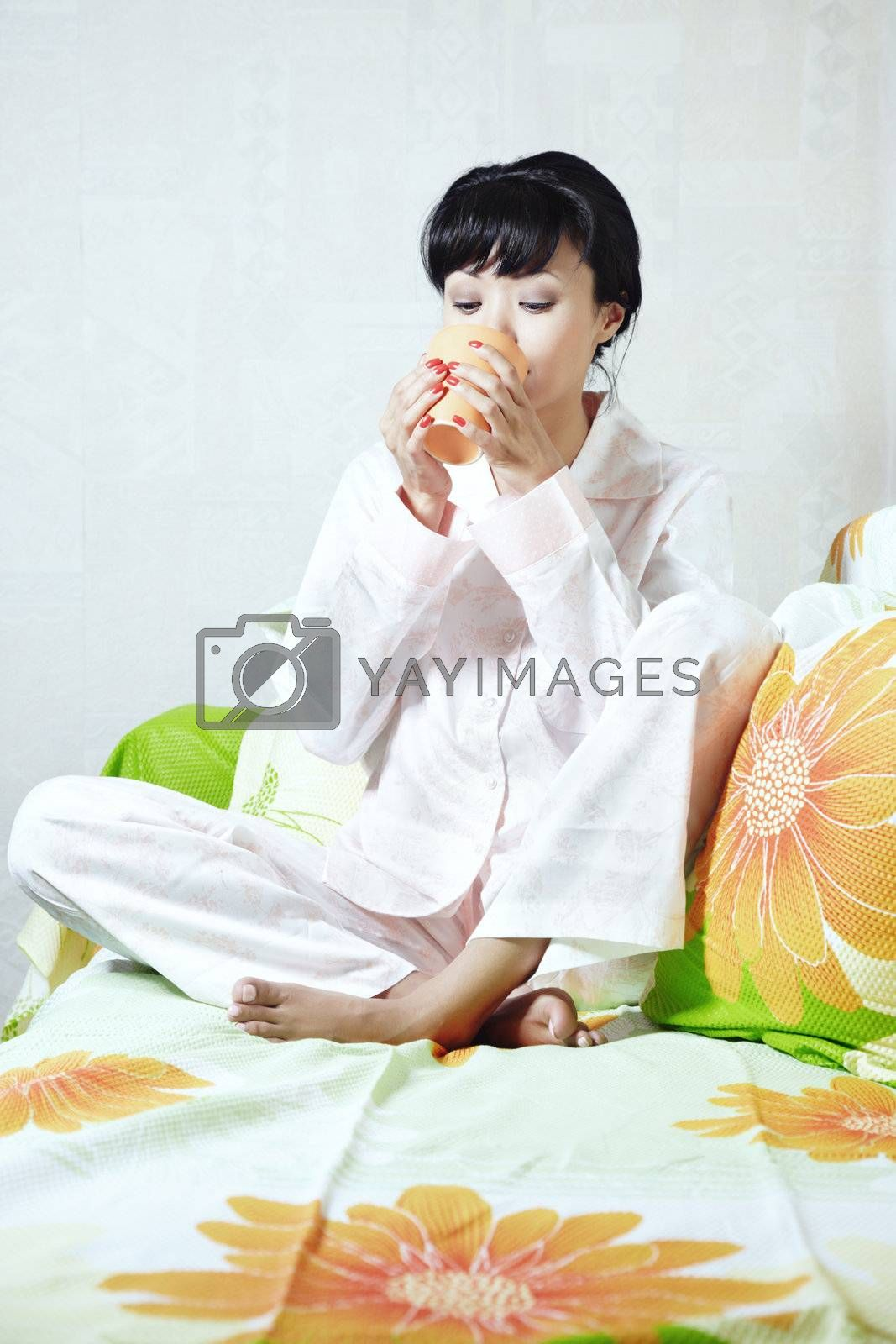 Brunette indoors drinking on a sofa in domestic pijamas
