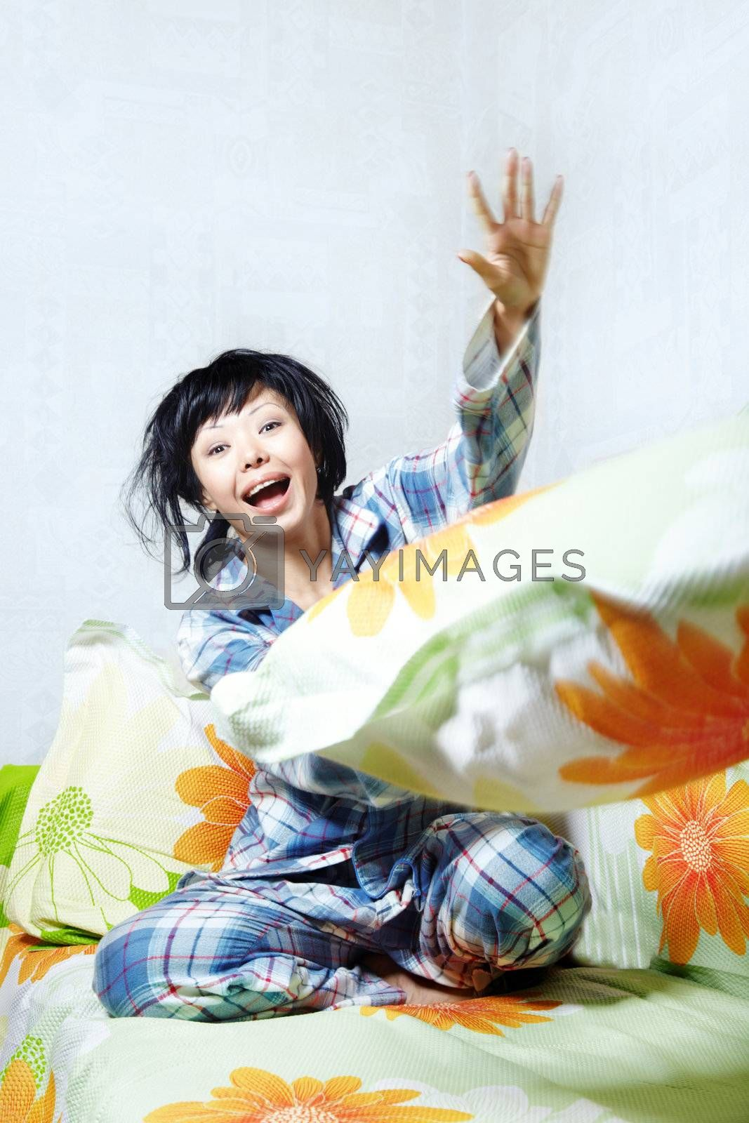 Laughing lady in pajamas playing with pillow