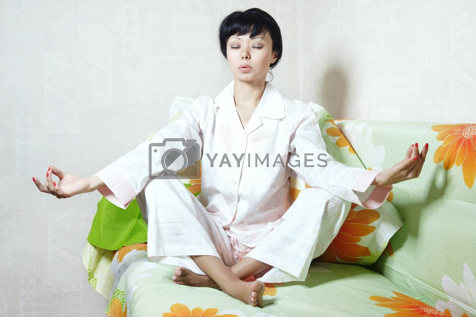 Lady sitting on the bed and doing yoga meditation