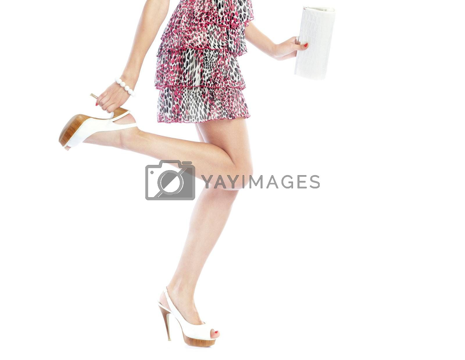 Part of the woman in dress posing on a white background and holding handbag