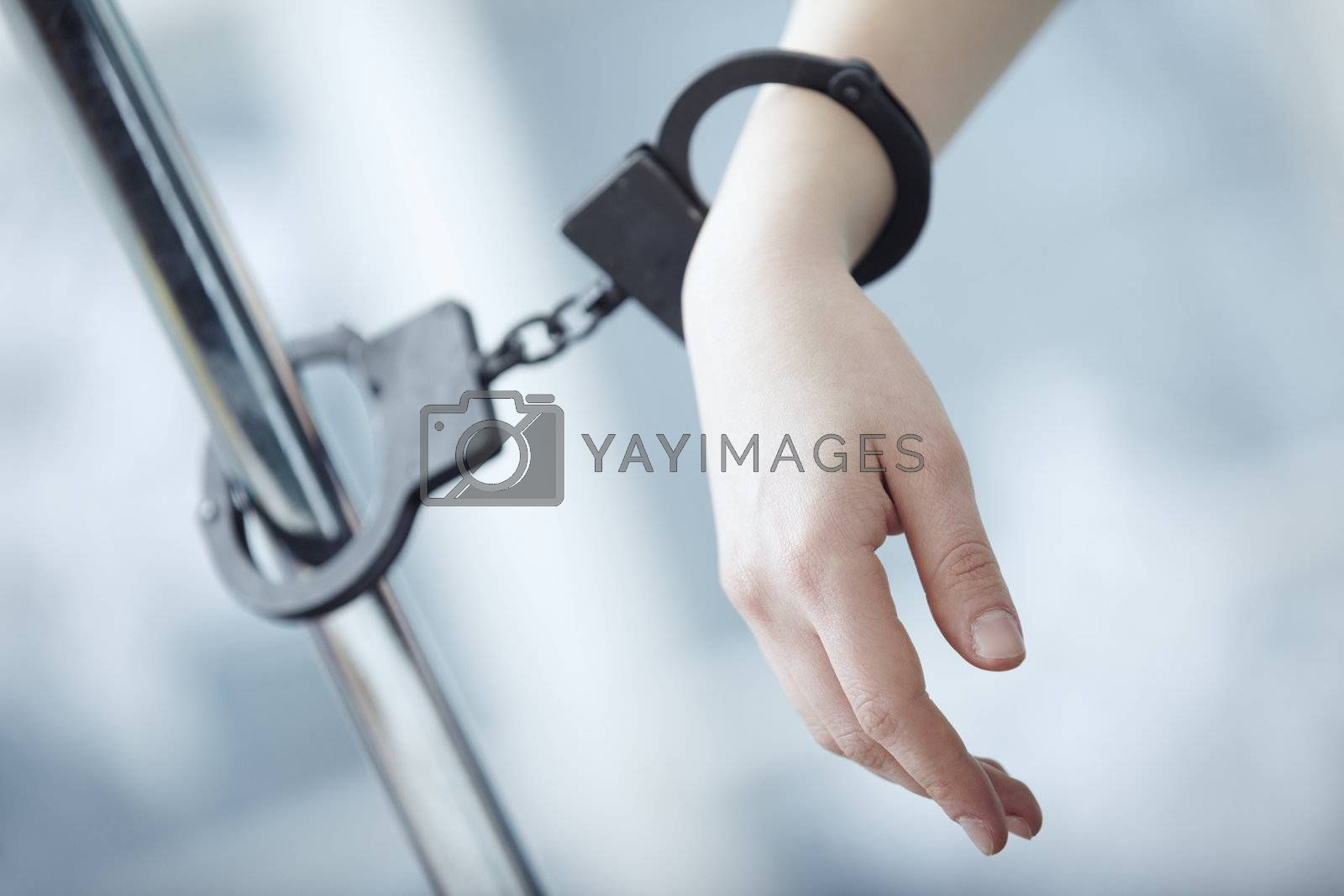 Human hand bounded to the metal pole by handcuffs