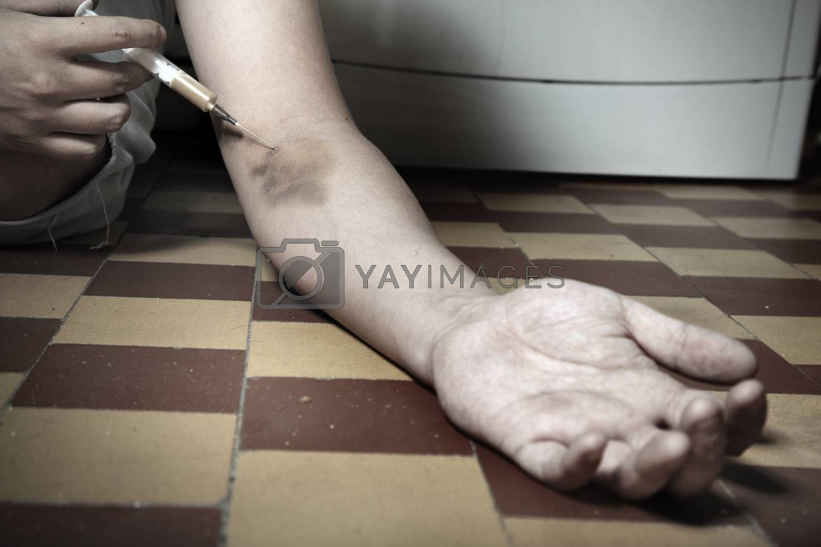 Hand of the narcotist with syringe on the floor. Artistic colors added