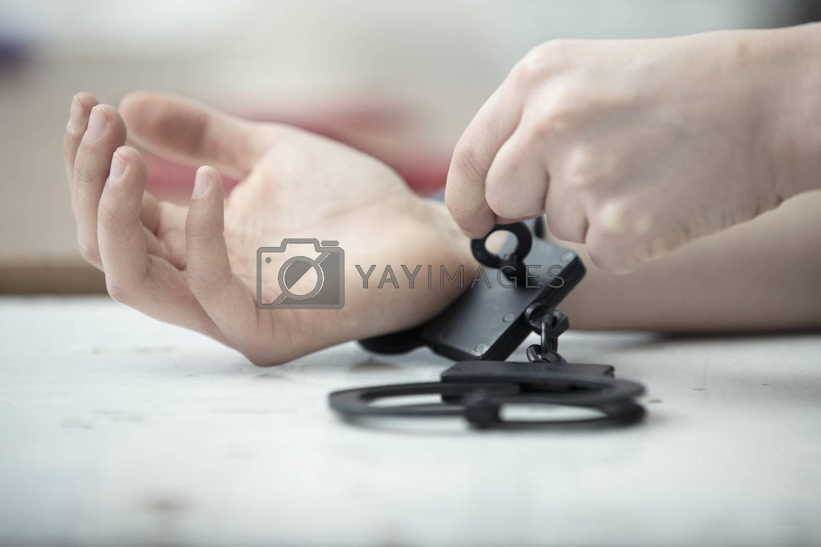 Human hands opening handcuffs