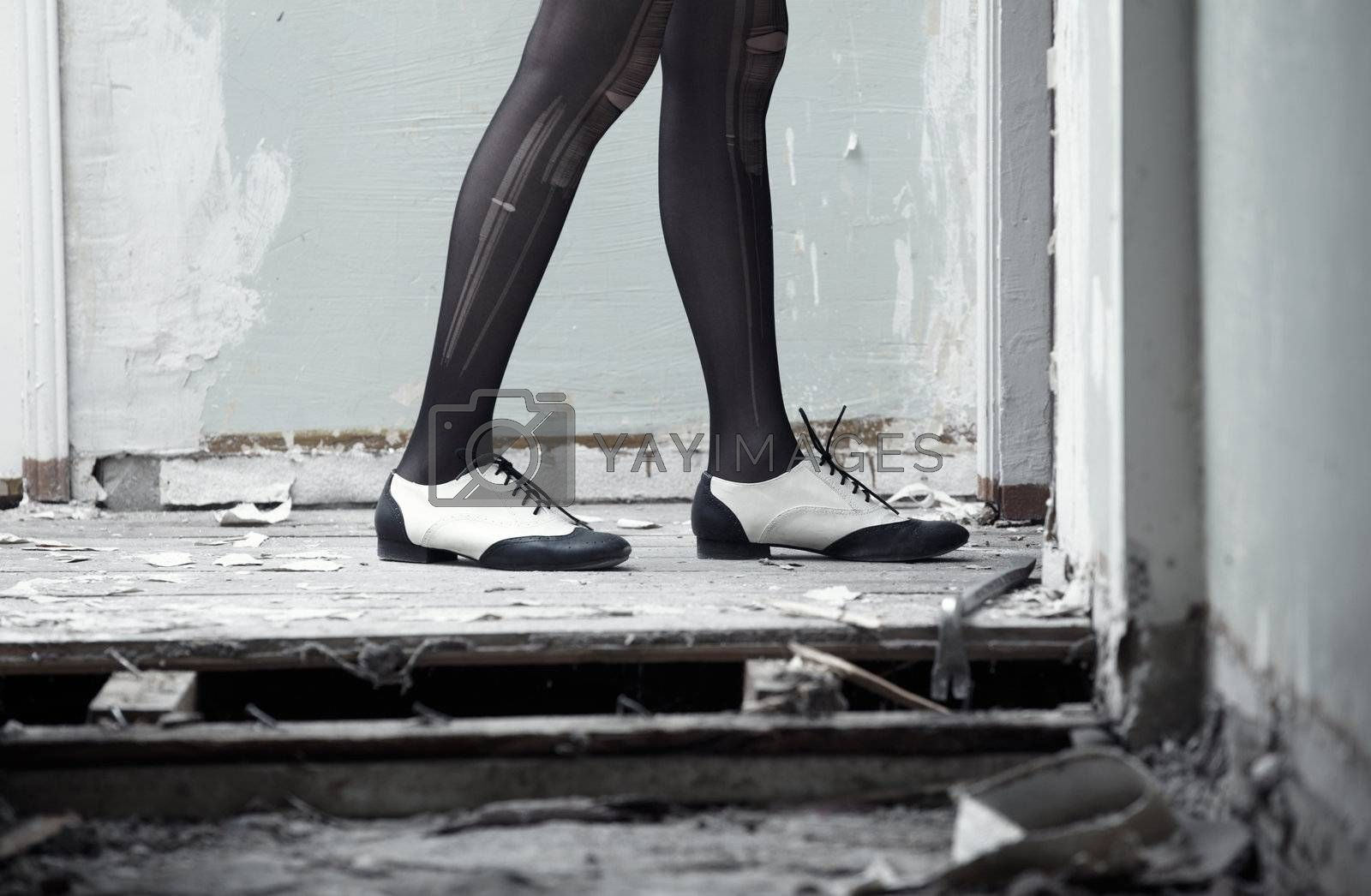 Human legs in stylish shoes standing on the old dirty wooden floor