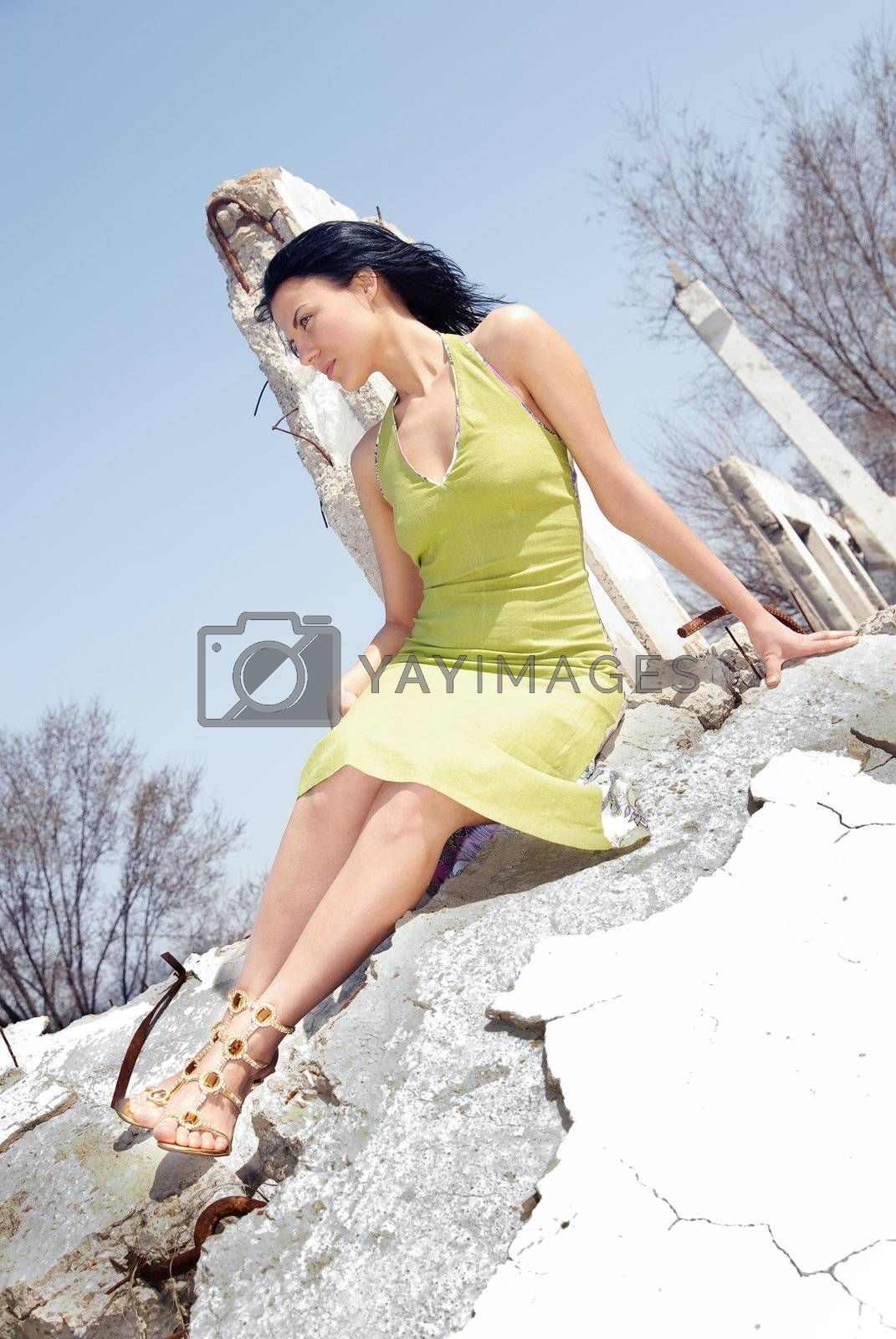 Glamour photo of the sexy lady sitting in stony ruins