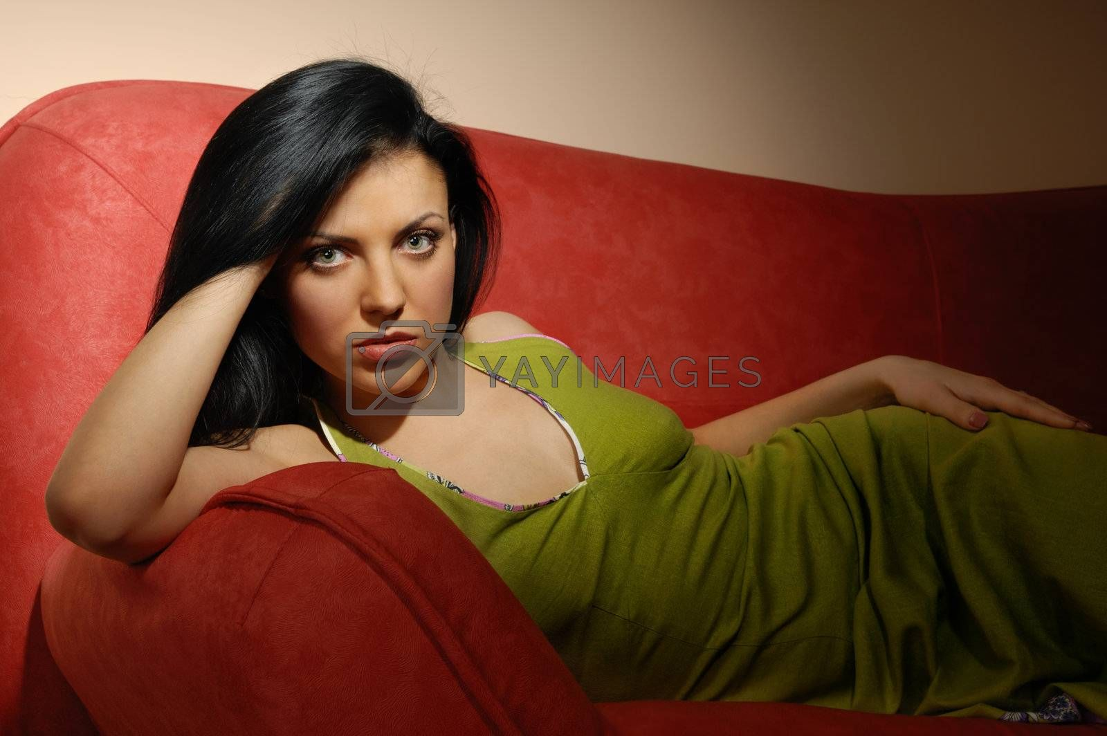 Elegant model laying on the red sofa in dark room