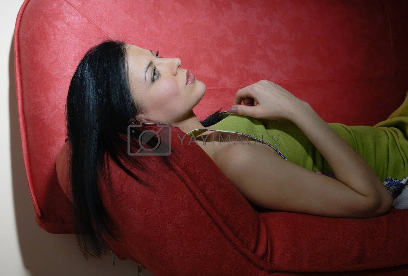 Portrait of the resting lady laying on the red sofa