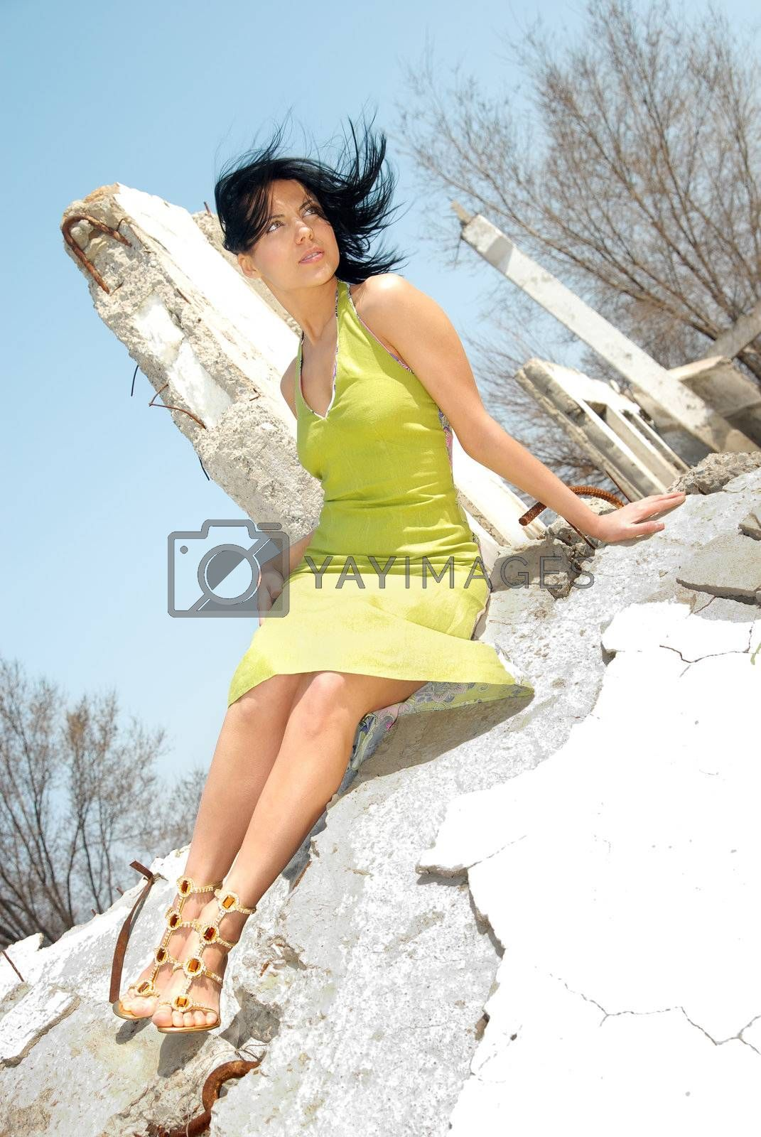 Sexy woman sitting on the stone ruins of old building