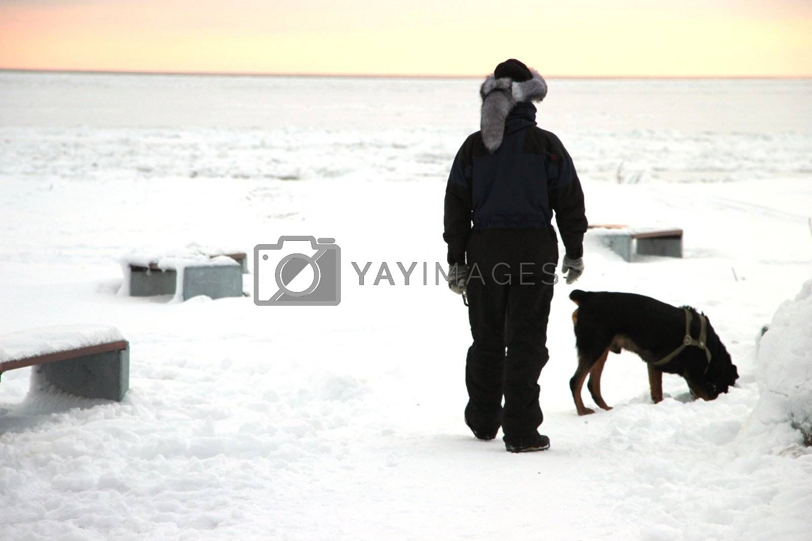 Men with rottweiler. Winter view to the beach