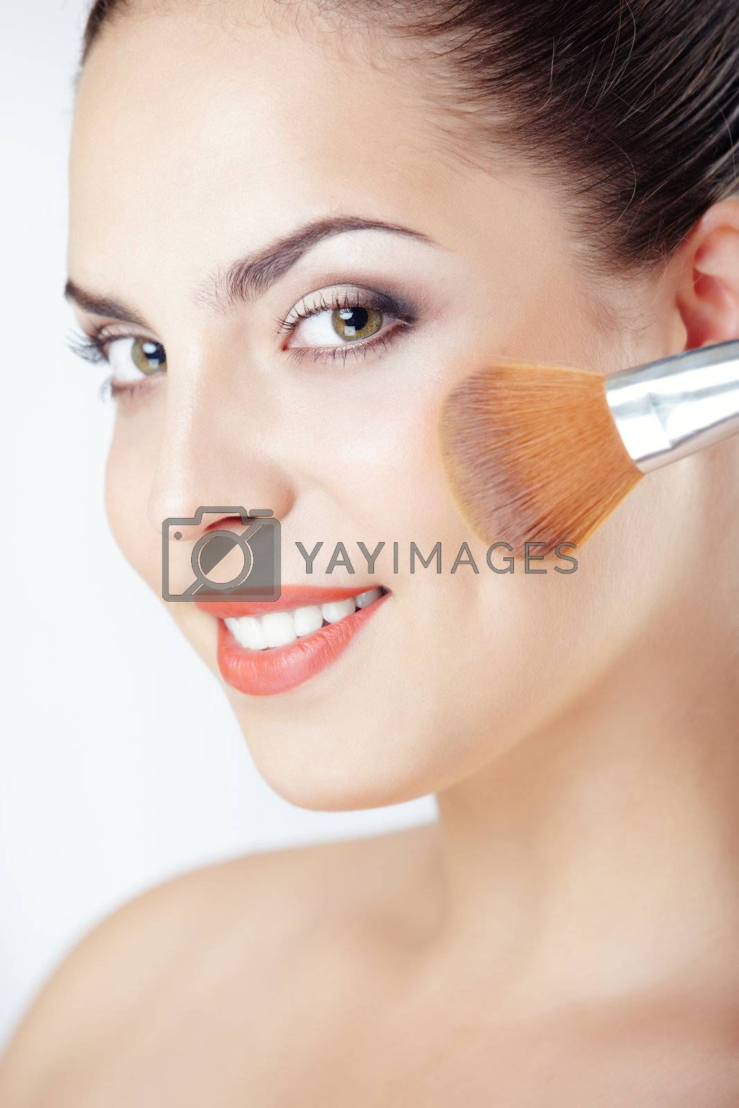 Smiling lady applies makeup brush on a studio background