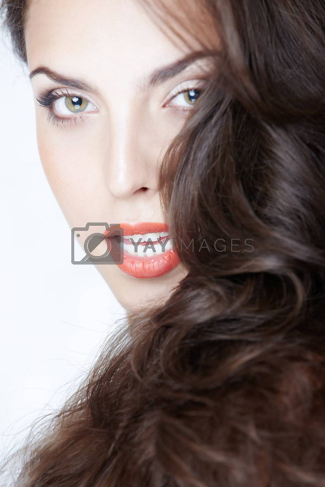 Beautiful lady with perfect makeup and curly hairs on a studio background