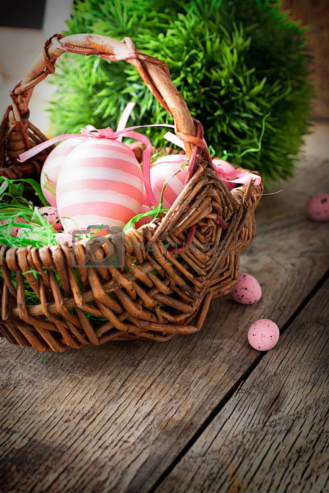 Colorful Easter holiday concept with pink eggs in wisker basket in nature