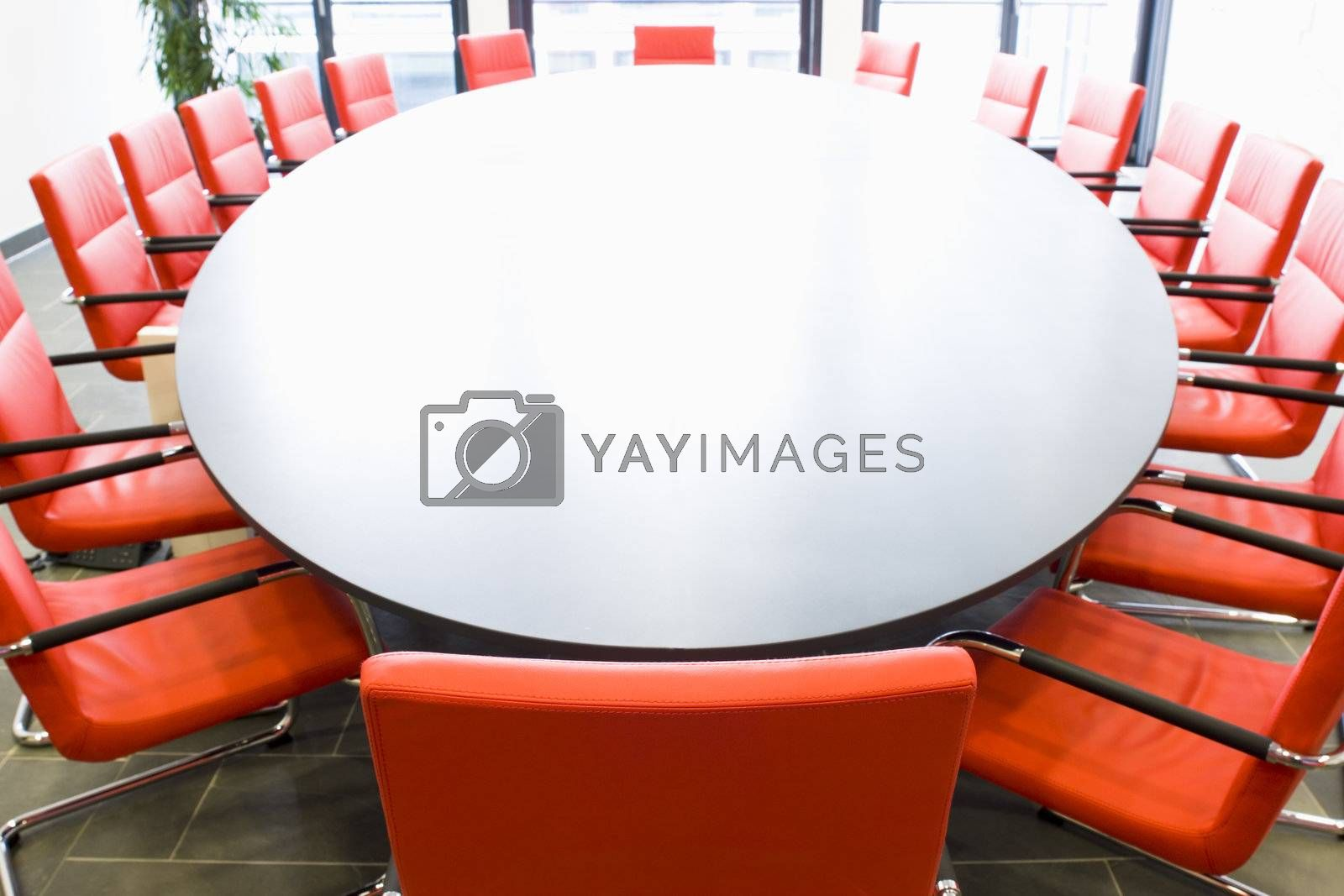 Meeting room with red chairs and oval conference table, Focus on the chair in the foreground