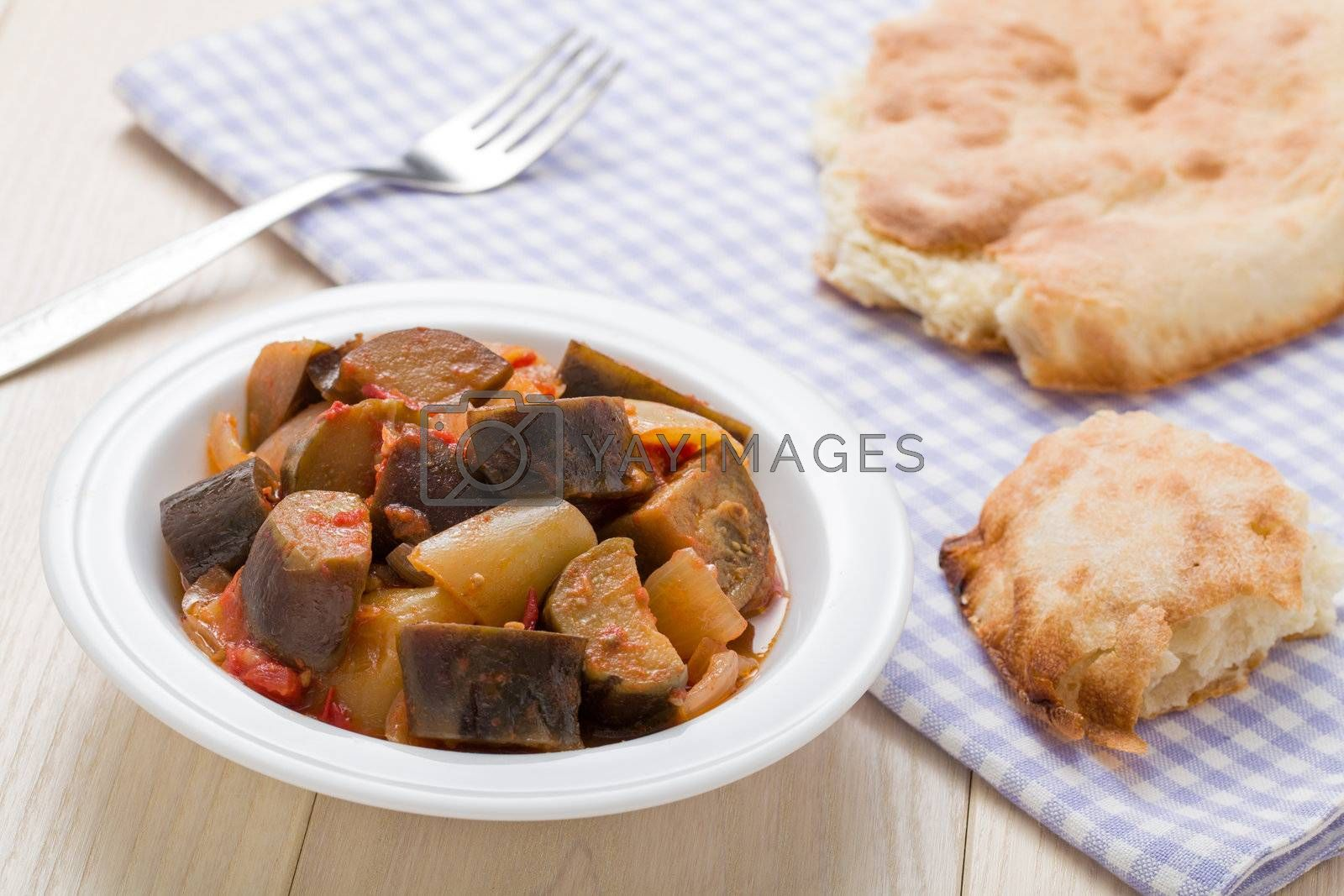 Cooked stewed eggplants in plate served with bread, fork on linen napkin and wooden table