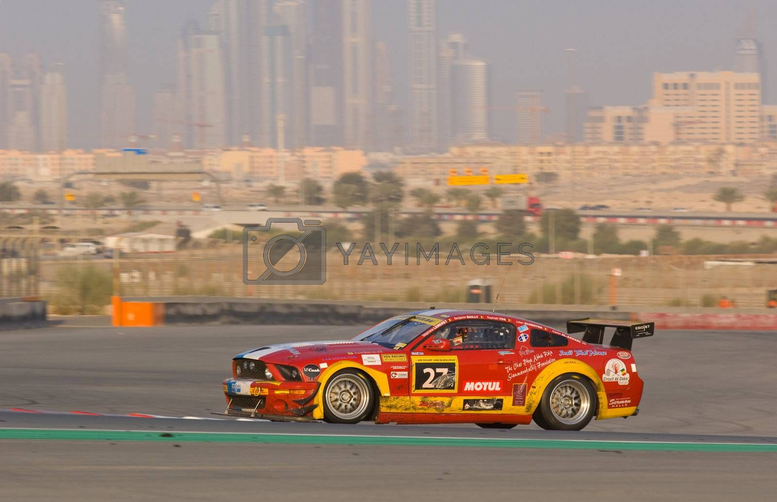 DUBAI - JANUARY 14: Car 27, a red Ford Mustang with Dubai City in the background, during the 2012 Dunlop 24 Hour Race at Dubai Autodrome on January 14, 2012.