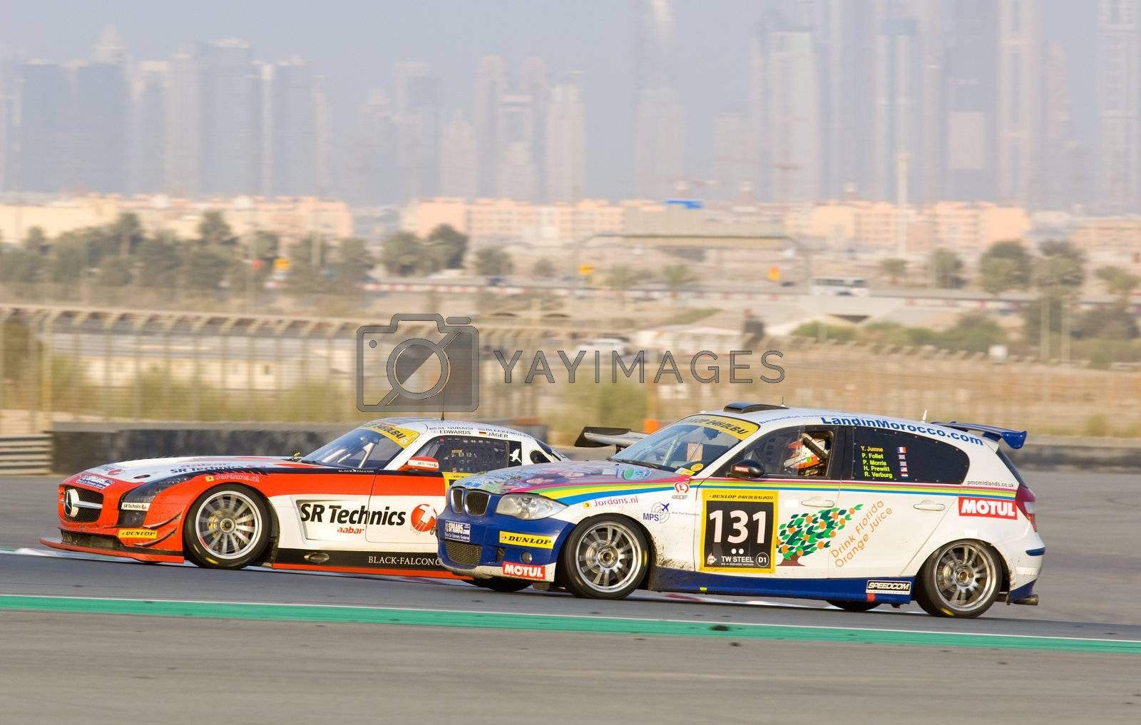 DUBAI - JANUARY 14: Mercedes SLS AMG GT3 and BMW 120D with Dubai City in the background, during the 2012 Dunlop 24 Hour Race at Dubai Autodrome on January 14, 2012.
